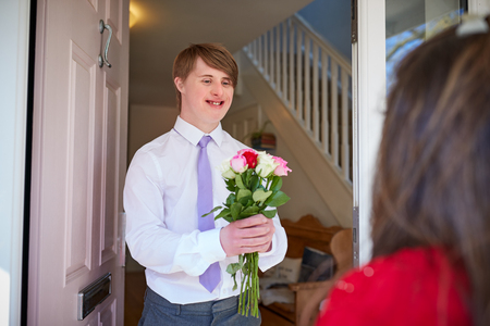 Loving Young Downs Syndrome Couple At Front Door With Man Giving Woman Flowers