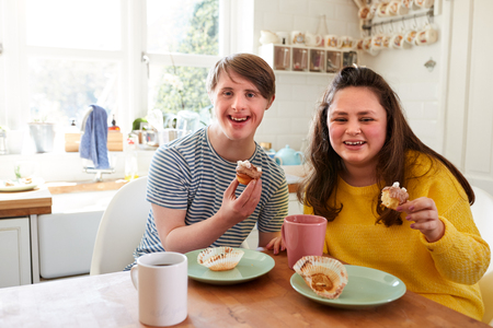 Portrait Of Young Downs Syndrome Couple Enjoying Tea And Cake In Kitchen At Home