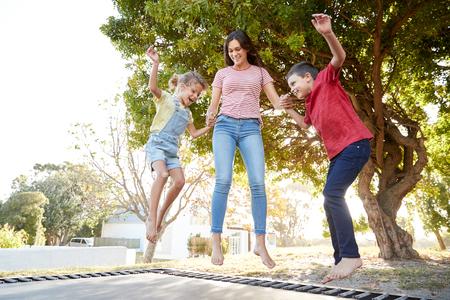 Hermanos con hermana adolescente jugando en el trampolín al aire libre en el jardín