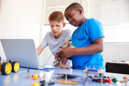 Deux étudiants masculins construisant et programmant un véhicule robot en classe de codage informatique après l'école Banque d'images