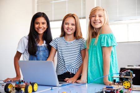 Portrait Of Three Female Students Building And Programing Robot Vehicle In School Computer Class