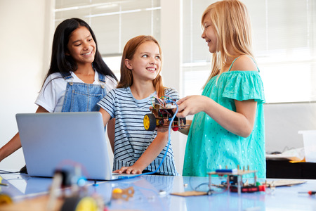 Three Female Students Building And Programing Robot Vehicle In After School Computer Coding Class Stock Photo