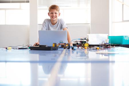 Portrait Of Male Student Building And Programing Robot Vehicle In School Computer Coding Class Stock Photo - 124373079