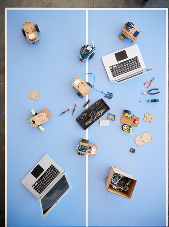Overhead View Of Laptops And Robotic Vehicles On Table In School Computer Coding Class