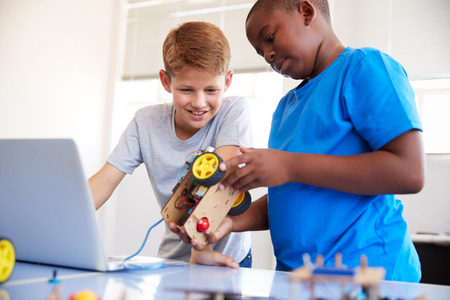 Two Male Students Building And Programing Robot Vehicle In After School Computer Coding Class