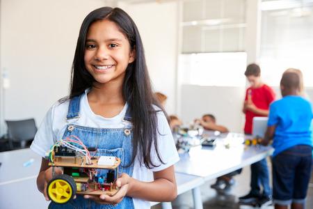 Retrato de estudiante de sexo femenino en el edificio del vehículo robot después de la escuela Clase de codificación informática
