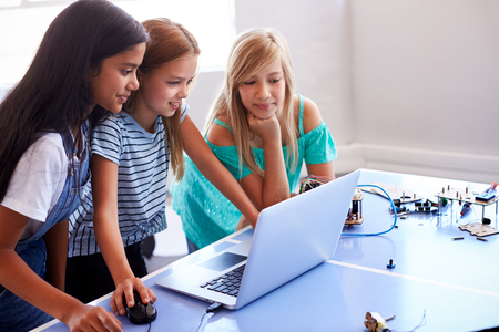Three Female Students Building And Programing Robot Vehicle In After School Computer Coding Class Banco de Imagens