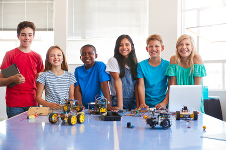 Ritratto di studenti di sesso maschile e femminile che costruiscono un veicolo robot dopo la classe di codifica del computer dopo la scuola