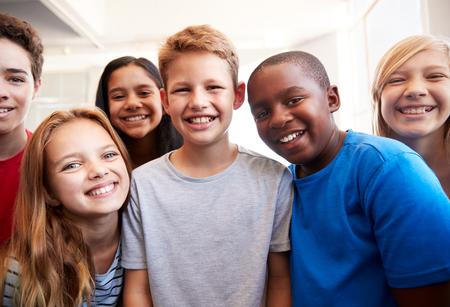 Portret van lachende mannelijke en vrouwelijke studenten in de klas van de lagere school