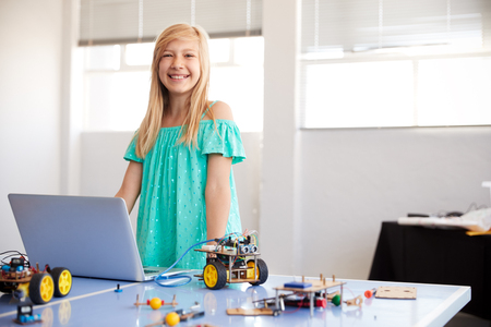 Portrait Of Female Student Building And Programing Robot Vehicle In School Computer Coding Class Stock Photo - 124373282