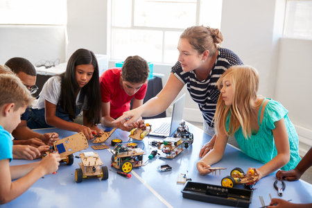 Élèves en classe de codage informatique après l'école et apprenant à programmer un véhicule robot