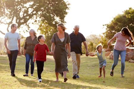 Familie mit mehreren Generationen, die gegen die pralle Sonne in der Landschaft spazieren