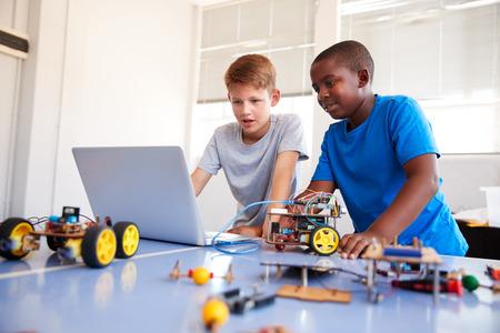 Dos estudiantes varones construyendo y programando un vehículo robot en la clase de codificación informática después de la escuela Foto de archivo