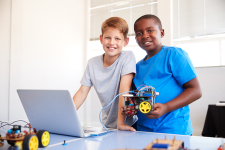 Portrait Of Two Male Students Building And Programing Robot Vehicle In School Computer Coding Class Stock Photo - 124373387