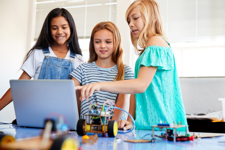 Three Female Students Building And Programing Robot Vehicle In After School Computer Coding Class 版權商用圖片