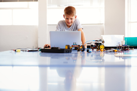 Male Student Building And Programing Robot Vehicle In School Computer Coding Class Stock Photo