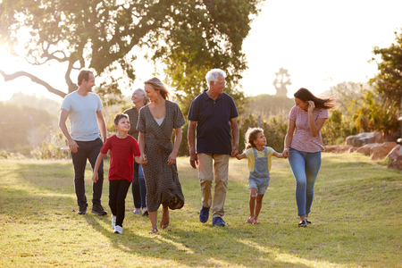 Multi-Generation Family Walking In Countryside Against Flaring Sun Stock Photo