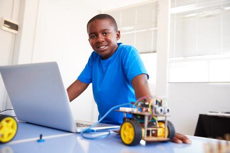 Portrait of Male Student Building et programmation du véhicule robot en classe de codage informatique de l'école Banque d'images