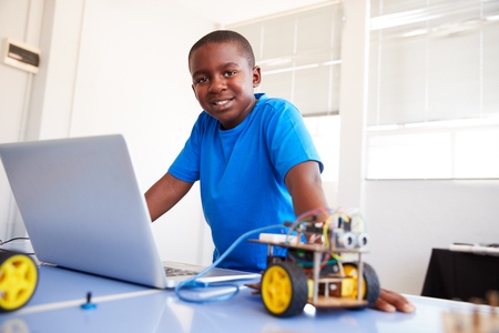 Portrait Of Male Student Building And Programing Robot Vehicle In School Computer Coding Class