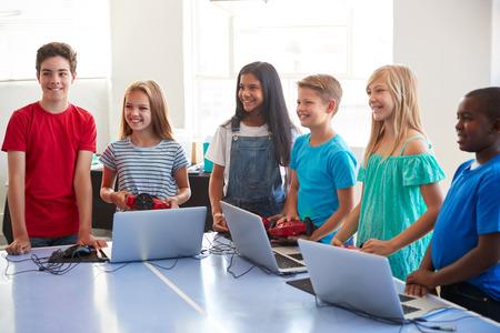 Gruppe von Schülern in der Computer-Codierungsklasse nach der Schule, die lernen, Roboterfahrzeuge zu programmieren