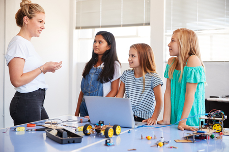 Three Female Students With Teacher Building Robot Vehicle In After School Computer Coding Class Banque d'images