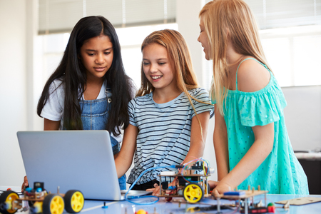Three Female Students Building And Programing Robot Vehicle In After School Computer Coding Class Stock Photo - 124373490