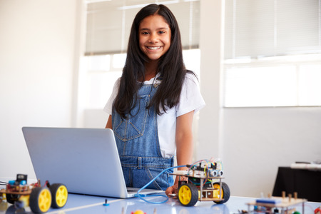 Portrait Of Female Student Building And Programing Robot Vehicle In School Computer Coding Class Stock Photo - 124373505