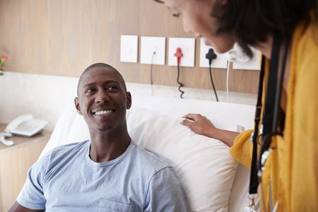 Medico con tavoletta digitale visita e parla con paziente maschio nel letto d'ospedale