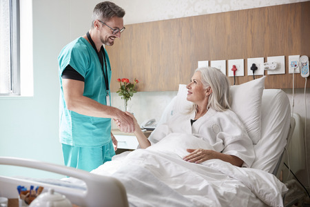 Surgeon Visiting And Shaking Hands With Mature Female Patient In Hospital Bed 免版税图像