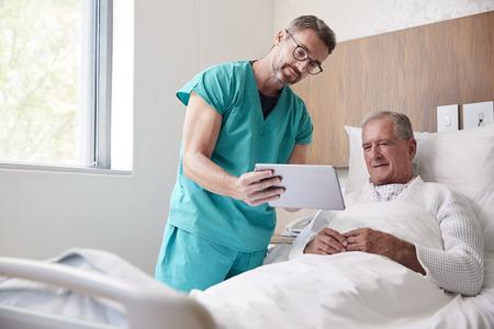 Chirurg mit digitalem Tablet, der älteren männlichen Patienten im Krankenhausbett in der geriatrischen Abteilung besucht Standard-Bild