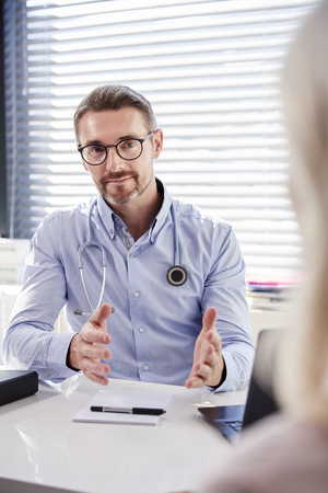 Mature Female Patient In Consultation With Doctor Sitting At Desk In Office Foto de archivo