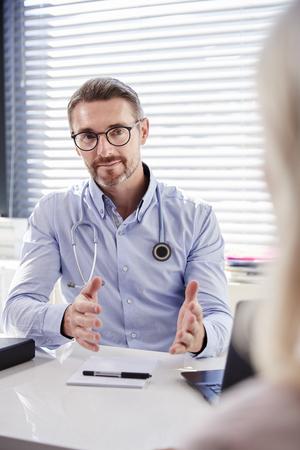 Patiente mature en consultation avec un médecin assis au bureau au bureau Banque d'images