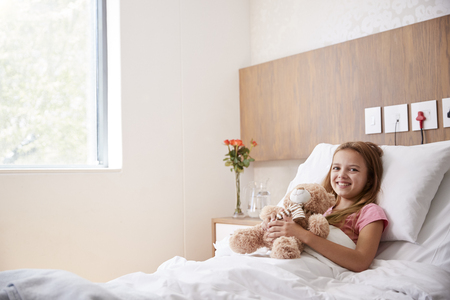 Portrait Of Girl Lying In Bed In Hospital Ward Hugging Teddy Bear