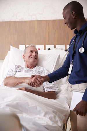 Doctor Shaking Hands With Senior Male Patient In Hospital Bed In Geriatric Unit Stock Photo