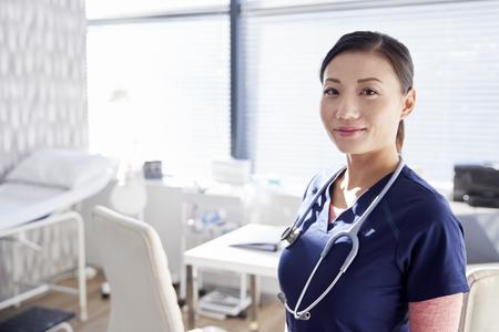 Retrato de mujer sonriente médico con estetoscopio por escritorio permanente en la oficina Foto de archivo