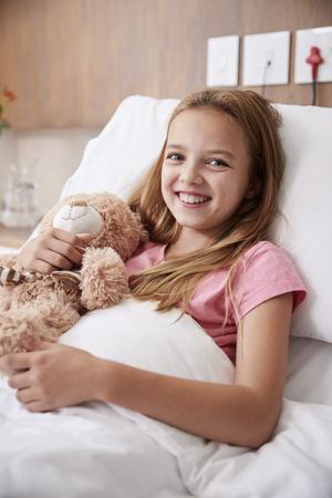 Retrato de niña acostada en la cama en la sala del hospital abrazando a un oso de peluche Foto de archivo