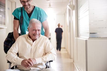 Maschio ordinato spingendo paziente maschio anziano dimesso dall'ospedale in sedia a rotelle Archivio Fotografico