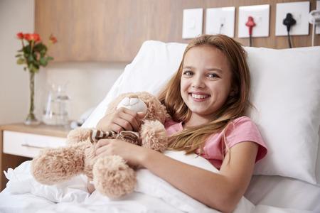Portrait Of Girl Lying In Bed In Hospital Ward Hugging Teddy Bear