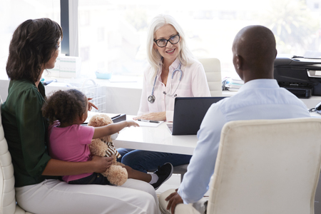 Family With Daughter In Consultation With Doctor In Office