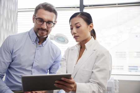 Female Doctor Showing Mature Male Patient Test Results On Digital Tablet In Office