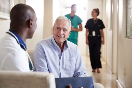 Dottore che accoglie un paziente di sesso maschile anziano che viene ricoverato in ospedale Archivio Fotografico