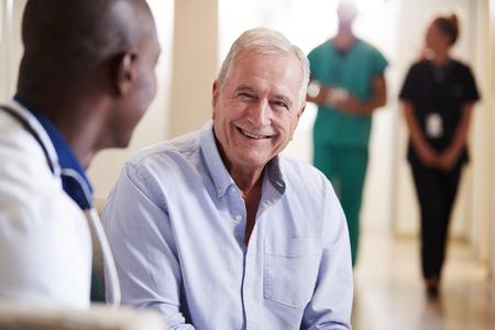 Dokter verwelkomt senior mannelijke patiënt die wordt opgenomen in het ziekenhuis
