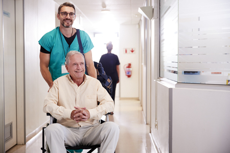 Male Orderly Pushing Senior Male Patient Being Discharged From Hospital In Wheelchair 写真素材