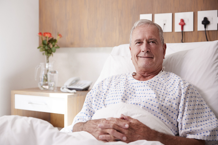 Portrait Of Male Senior Patient Lying In Hospital Bed Smiling At Camera Фото со стока