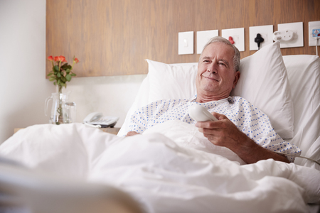 Male Senior Patient Lying In Hospital Bed Watching Television Stock fotó