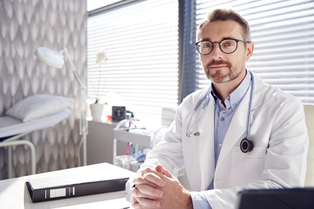 Portrait Of Smiling Male Doctor Wearing White Coat With Stethoscope Sitting Behind Desk In Office Stock fotó