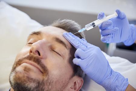 Vrouwelijke schoonheidsspecialiste geeft volwassen mannelijke patiënt Botox-injectie in voorhoofd