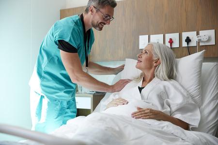 Chirurgien visitant et parlant avec une patiente mature dans un lit d'hôpital