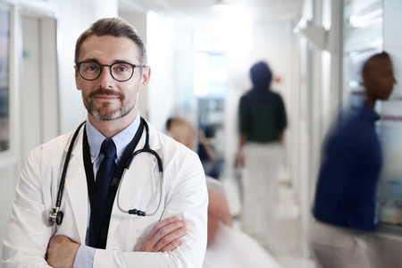 Portrait Of Mature Male Doctor Wearing White Coat With Stethoscope In Busy Hospital Corridor