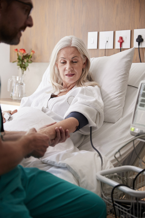 Male Nurse Taking Mature Female Patients Blood Pressure In Hospital Bed With Automated Machine 写真素材